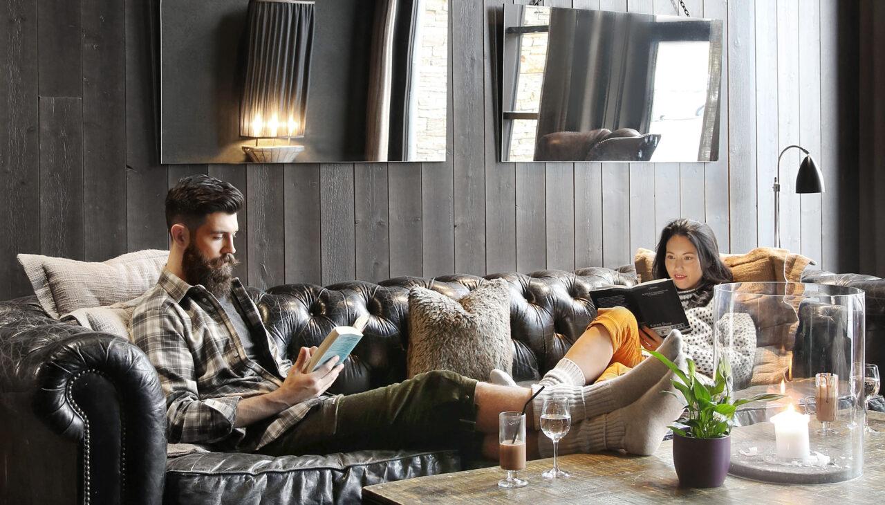 I biblioteket på hotellet på Norefjell Ski og Spa ligger det to stykker og slapper av med en god bok